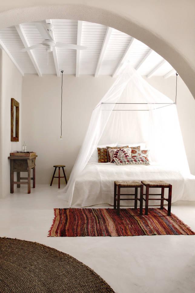 Оптимальный фон для спальни в греческом стиле - обычные белые стены с фактурной штукатуркой. Акцентом такого помещения может стать текстиль