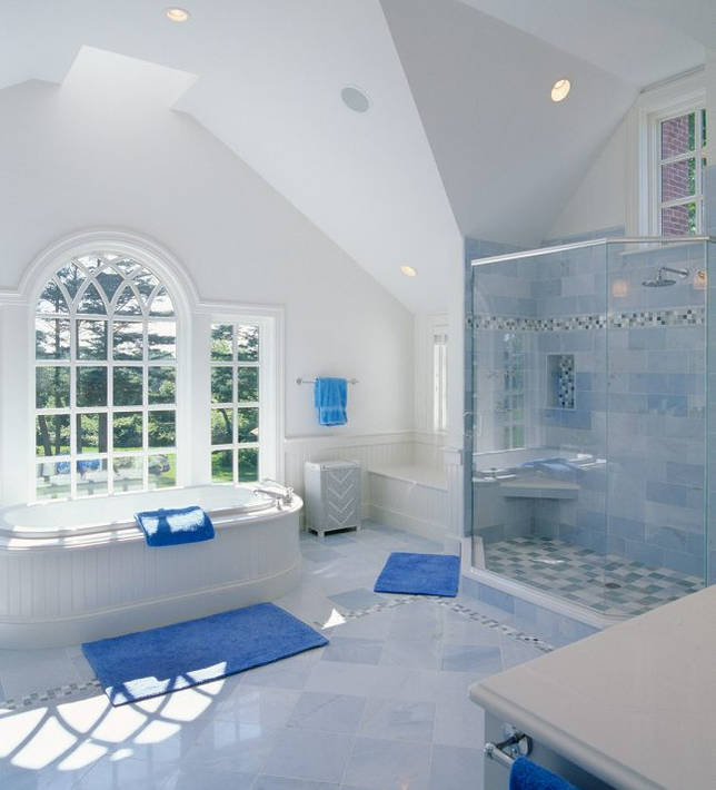 Просторная ванная в частном доме с белой сантехникой и яркими синими акцентами на элементах декоора