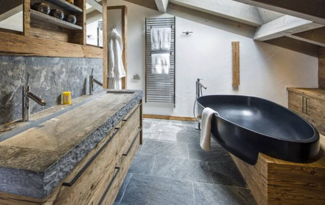 Черная чаша ванны в комнате загородного дома